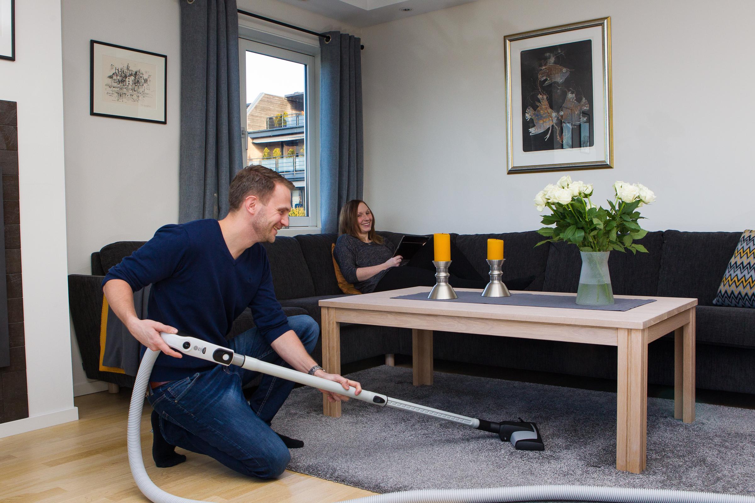 Man støvsuger under bordet i stuen med en sentralstøvsuger